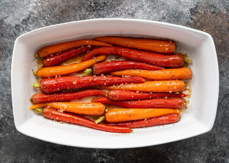 bright orange and red heirloom carrots in white rectangular baking dish