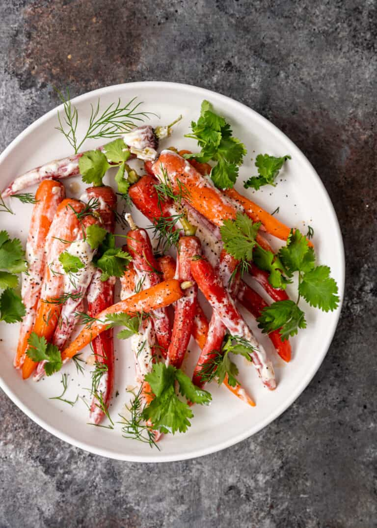 overhead: white platter of Moroccan carrots drizzled with creamy white sauce and fresh herbs