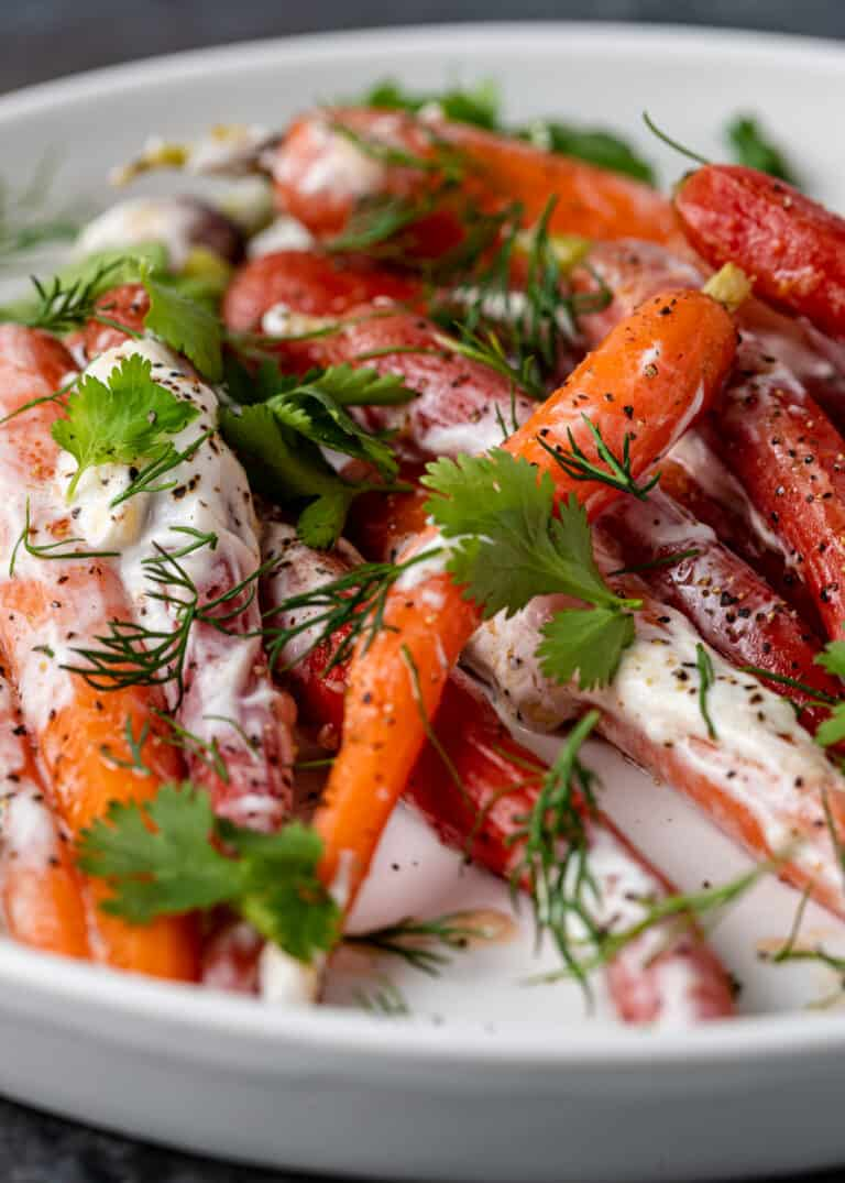 close up image of heirloom Moroccan carrots on white platter with fresh herbs