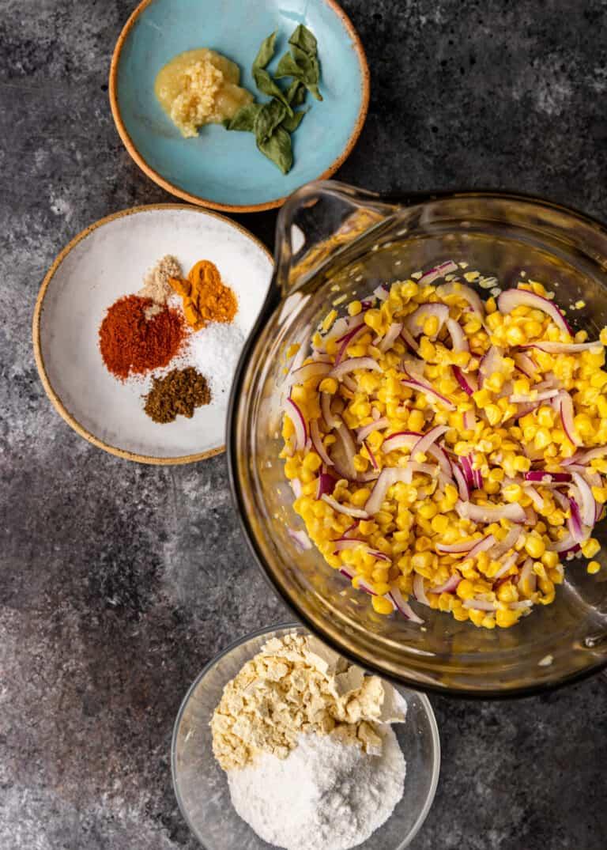 overhead: corn niblets, minced onion and spices to make pakoda recipe