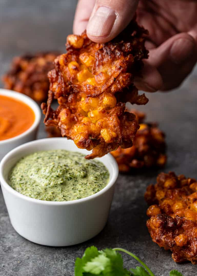 dipping Indian corn fritter into dish of creamy mint chutney