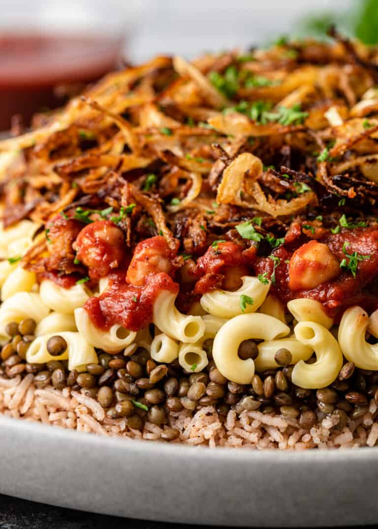 cooked basmati rice, brown lentils, and macaroni covered in tomato sauce with crispy fried onions on top