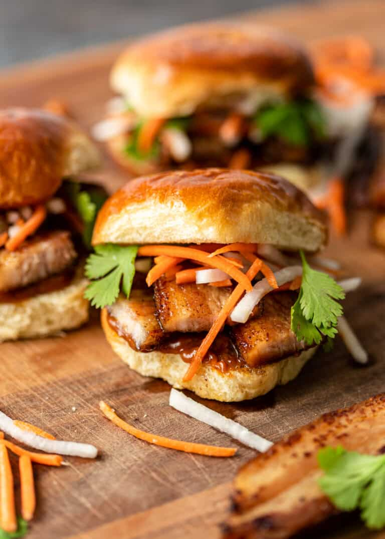 fried pork belly sliders topped with pickled vegetables on wood cutting board