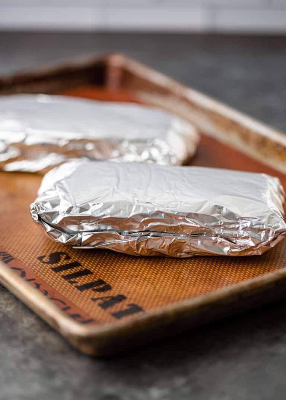 foil packets of pork on baking sheet