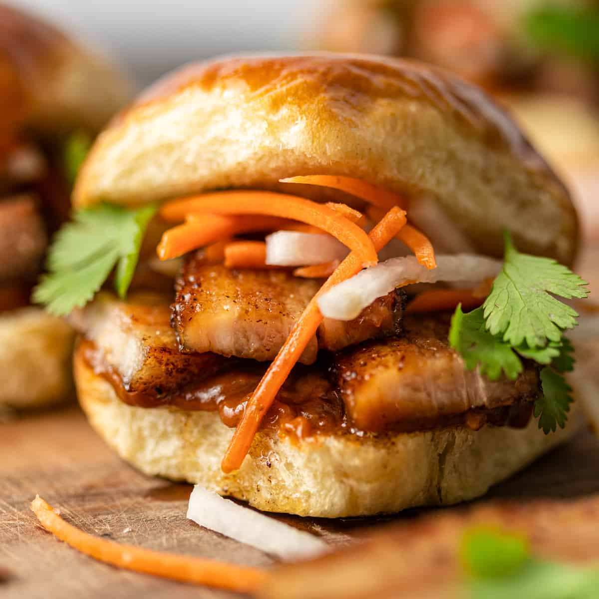 close up: fried pork belly on a soft bun with thin slices of carrots and onions