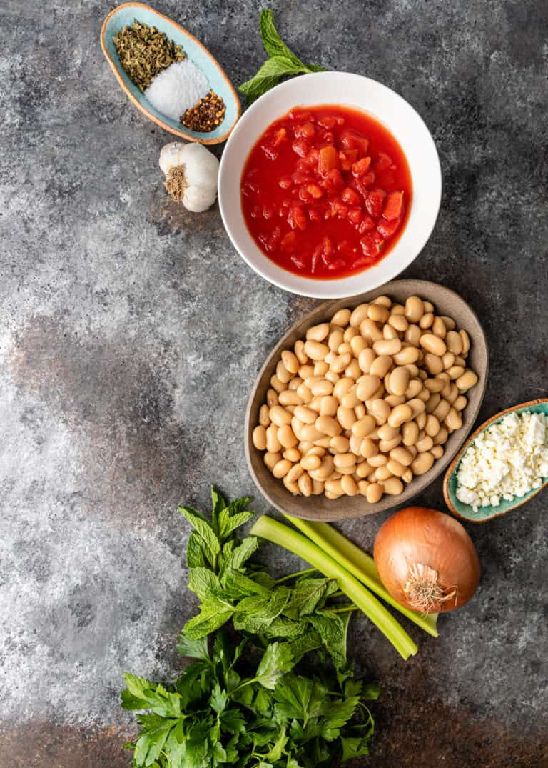 overhead image: bowls of dried Greek beans, crushed tomatoes, spices, and vegetables to make a healthy Mediterranean side dish