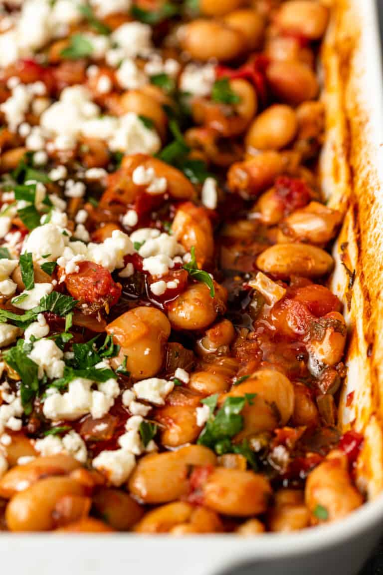 overhead image: casserole dish of baked Greek beans in tomato sauce with parsley and feta cheese