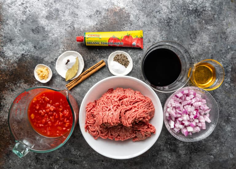bowl with raw ground meat and smaller bowls of ingredients for pastitsio recipe