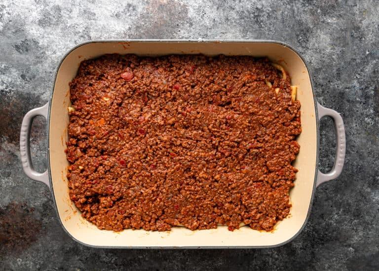 overhead: layer of meat sauce in casserole dish for pastitsio (greek lasagna)