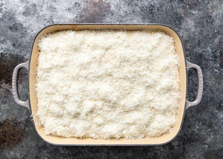 overhead: layer of shredded kefalotyri cheese in baking dish for pastitsio recipe