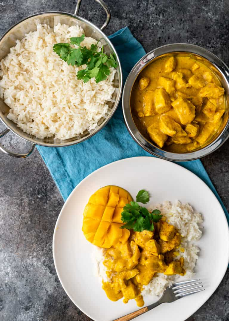 overhead: bowl of white rice next to bowl of mango chicken; plated dinner below bowls