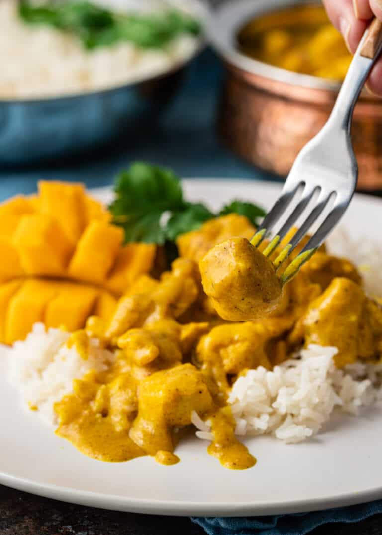 fork pierced into piece of yellow chicken curry on white plate