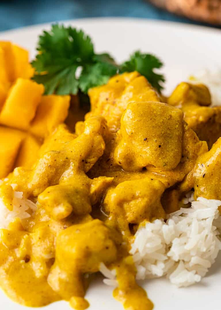 mango chicken indian curry served over rice on white plate