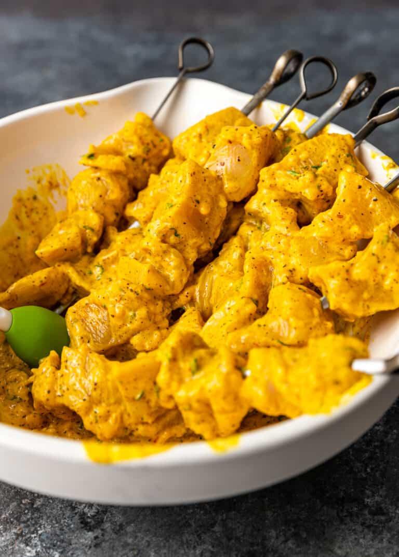 raw marinated pieces of saffron chicken threaded onto kabob skewers