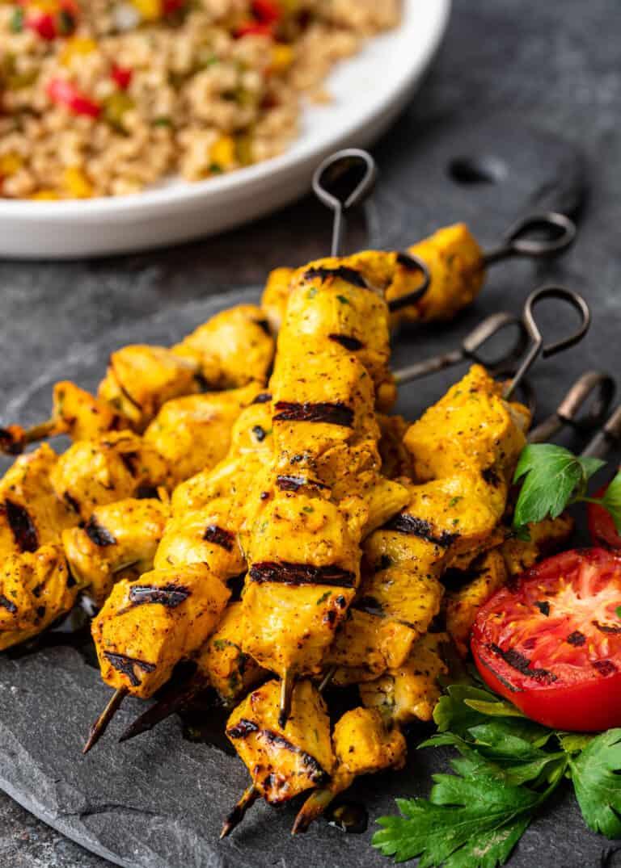 Persian chicken kabob dinner (on metal skewers) next to bowl of Israeli couscous