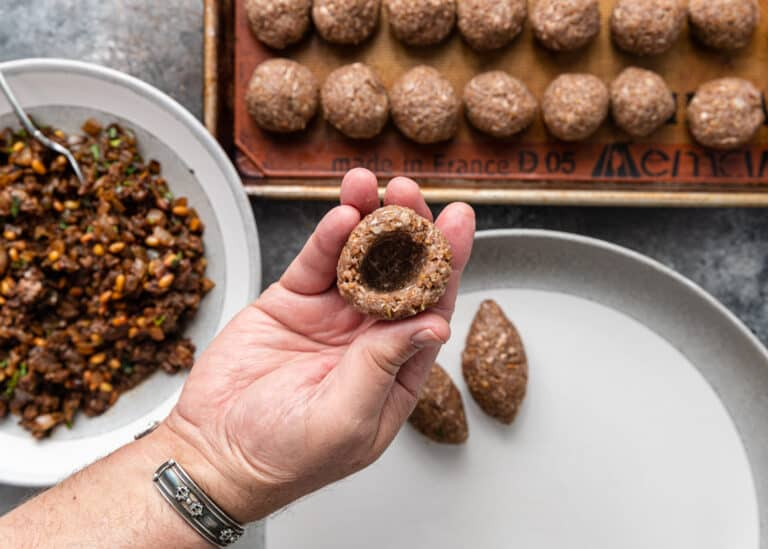 man's hand holding ball of ground meat with hole for filling
