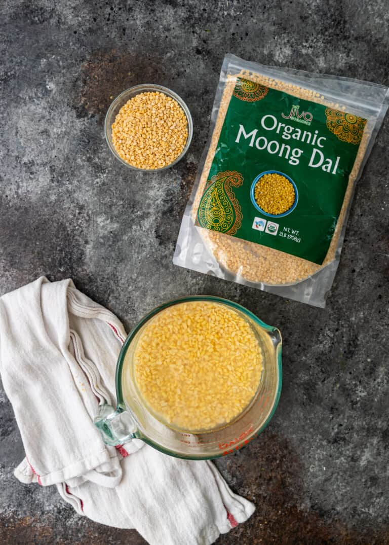 overhead: soaking dried organic moong dal in water. Package of the split mung beans next to it