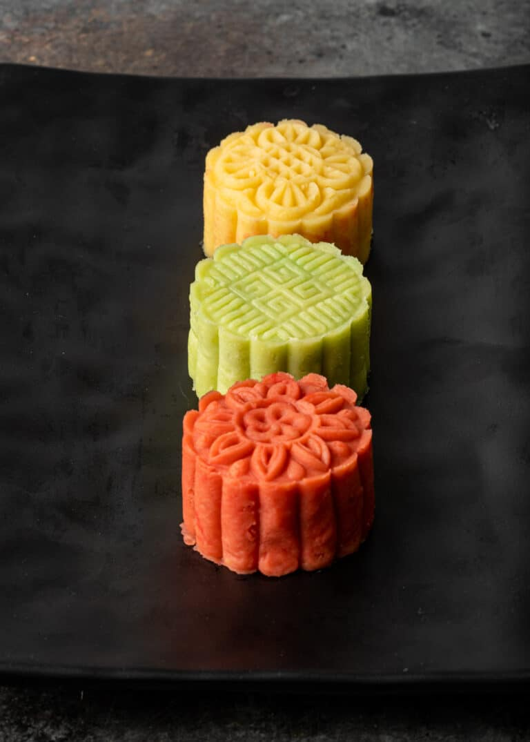 tiny yellow, green, and red bean paste desserts on black plate