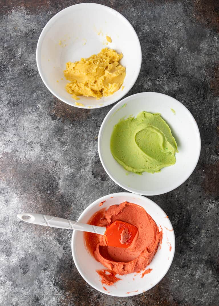 3 bowls of dough in colors of red, green and yellow made with natural food powder coloring