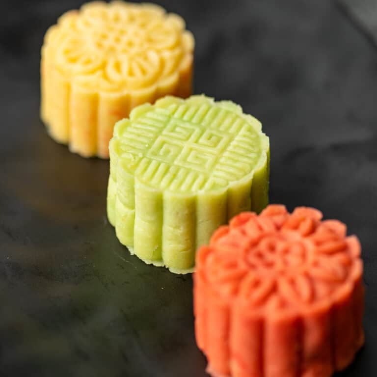 mung bean cake shown in 3 flavor and color combinations: yellow custard, green matcha, and red beet