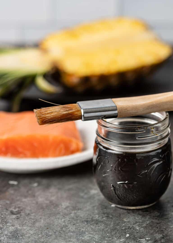 pineapple teriyaki sauce in small glass jar with basting brush on top