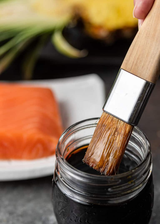 close up image of basting brush being dipped into jar of Asian marinade