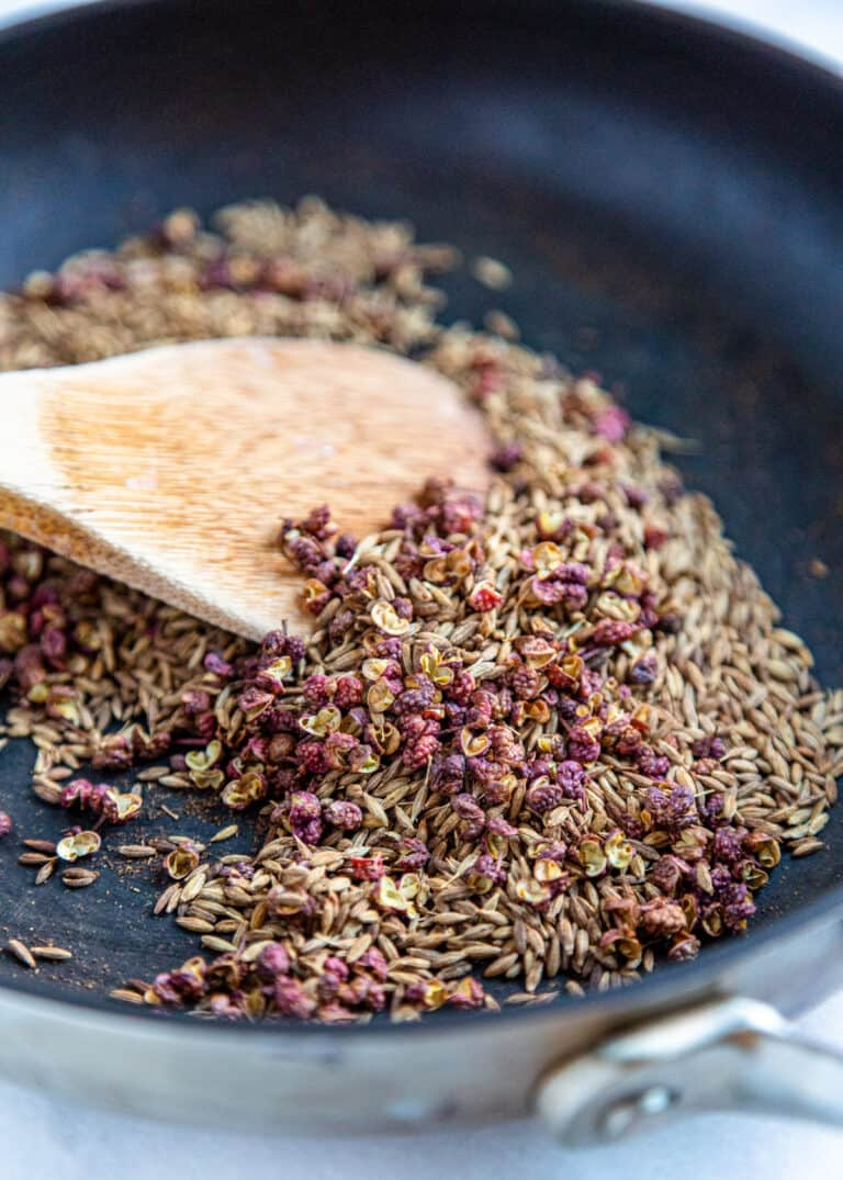 close up image: wooden spoon stirring Xinjiang spice blend
