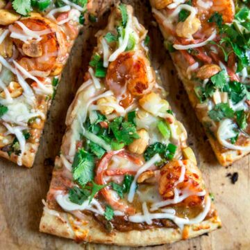 overhead image: close up of single slice of sweet and spicy shrimp on pizza with Thai peanut sauce