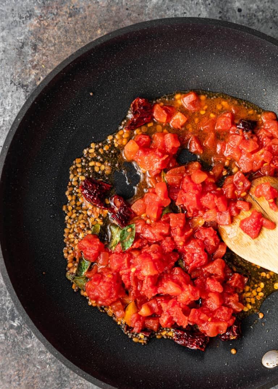 making a tomato chutney recipe in black skillet