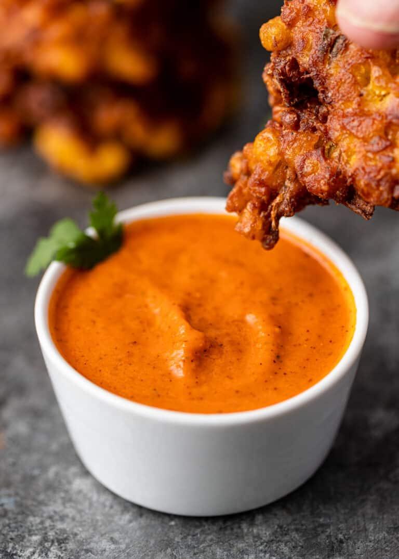 dipping vegetable pakora into Indian chutney