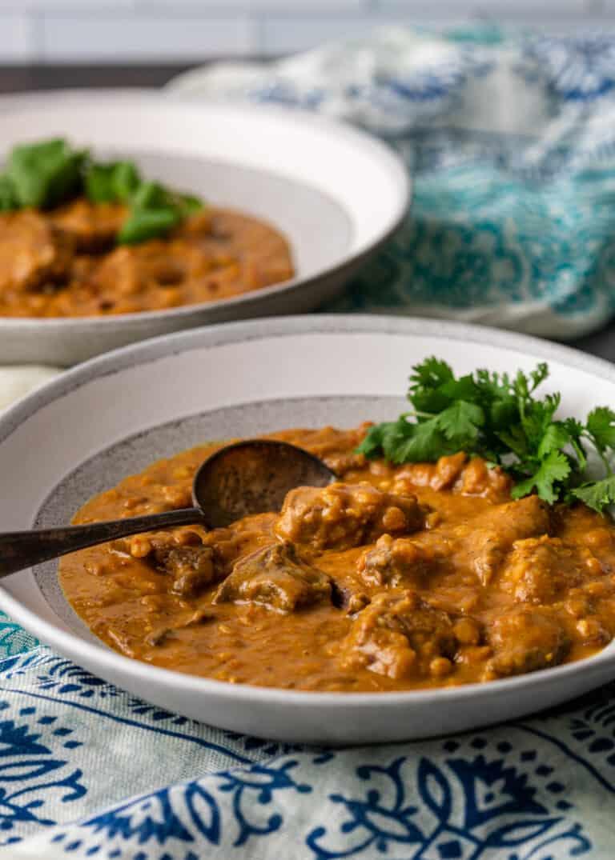 dal gosht lentil stew in shallow white bowl with spoon