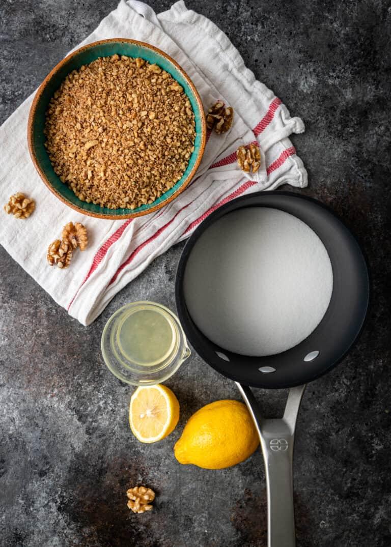 overhead image: bowls of walnuts and lemon juice next to saucepan of milk