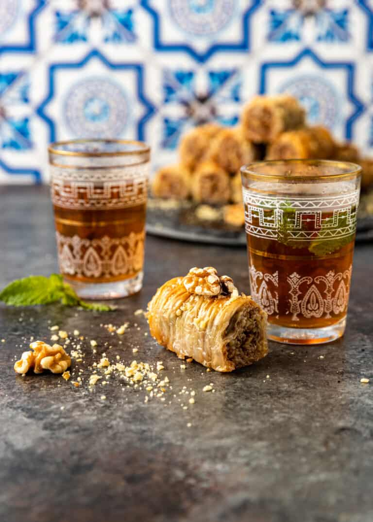 phyllo pastry dessert on kitchen counter with pieces of crushed walnuts