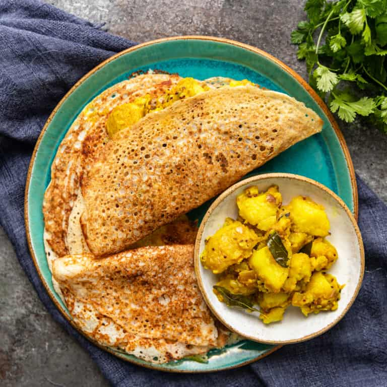 green plate with stack of Indian crepes and spicy potatoes