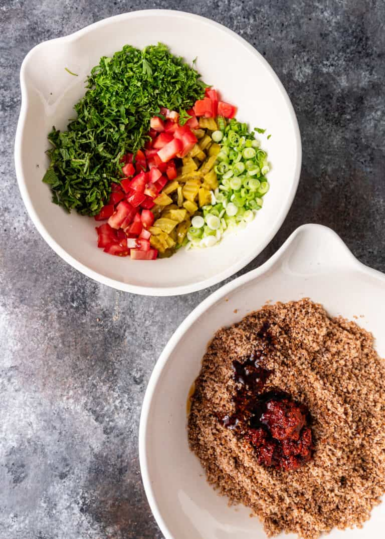 overhead: two white mixing bowls side by side. One with bulgur and one with chopped salad vegetables