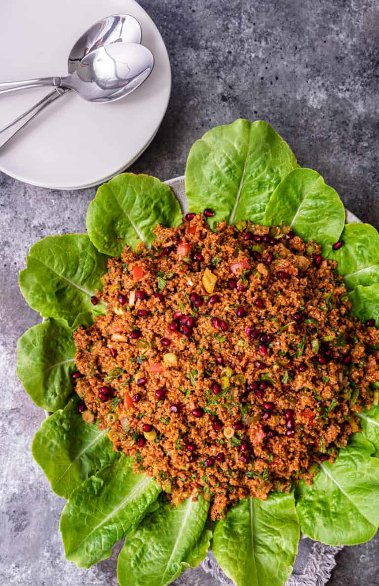 overhead: platter of turkish bulgur salad next to white serving plates and spoons