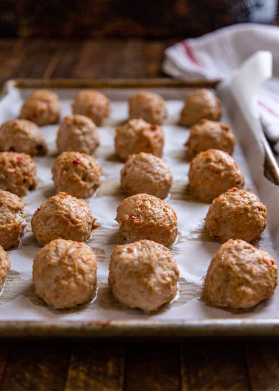 spicy ground chicken meatballs on baking sheet