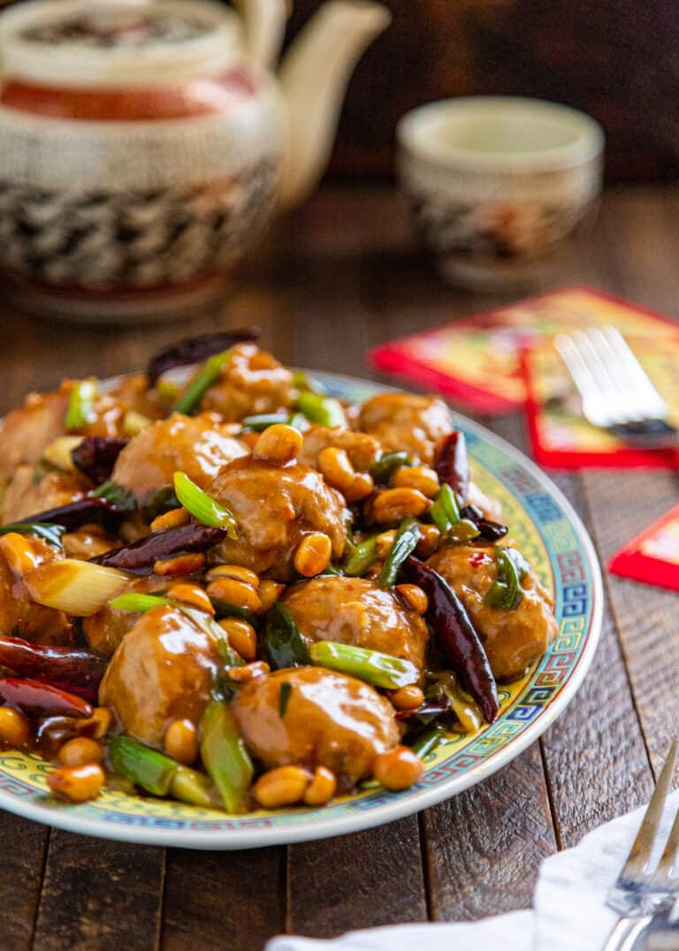 dish with spicy Chinese meatballs topped with peanuts, scallions and dried Chinese peppers