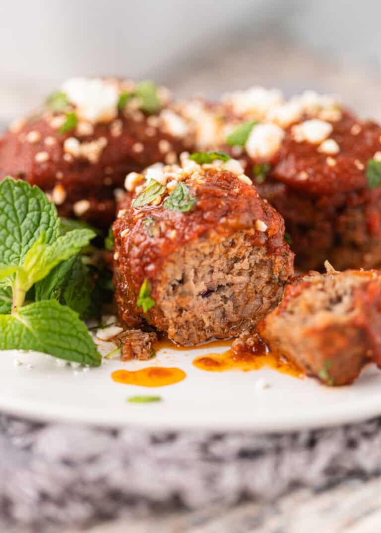 Greek beef meatballs on white plate, one in front is sliced open