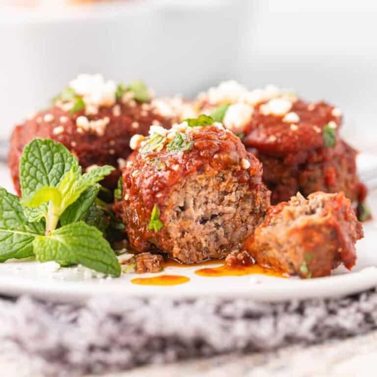 close up: soutzoukakia smyrneika served on white dinner plate
