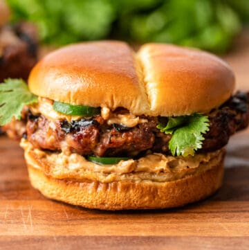 ground pork and beef burger with jalapenos and spicy peanut sauce on soft bun