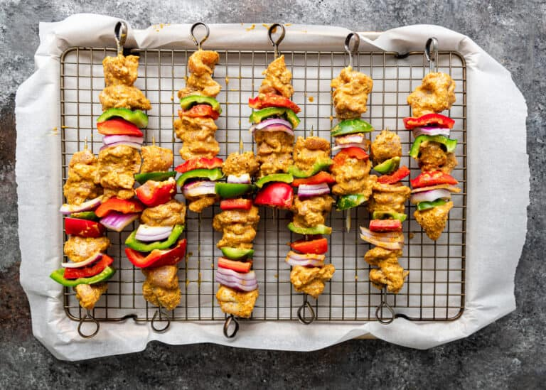 overhead: 5 skewers of tikka kabab ready for grilling