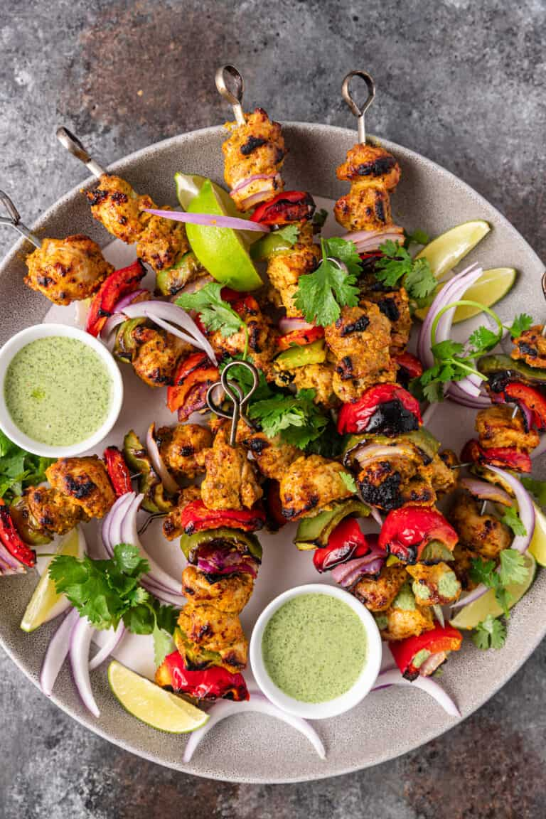 overhead: skewers of chicken tikka kebab and dipping sauce on round serving platter