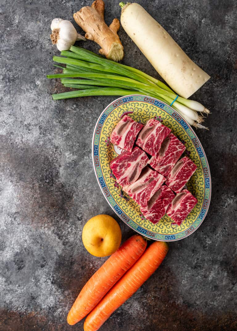 overhead: uncooked beef short ribs and root vegetables for galbi jjim recipe