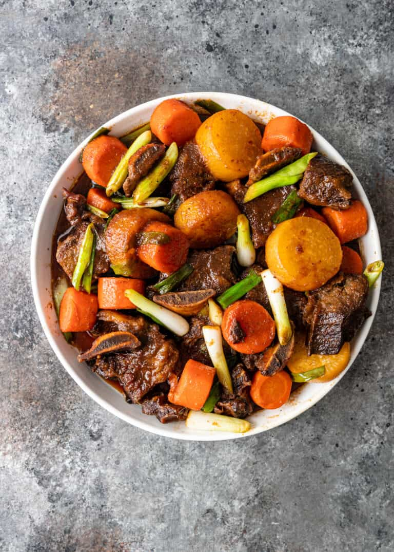 short ribs with carrots and potatoes in white bowl