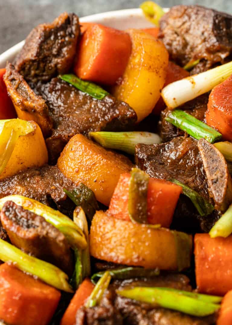 galbi jjim braised short ribs with carrots and scallions in white bowl