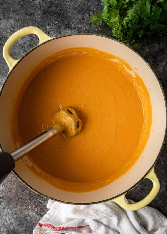 immersion blender pureeing pot of red lentil soup