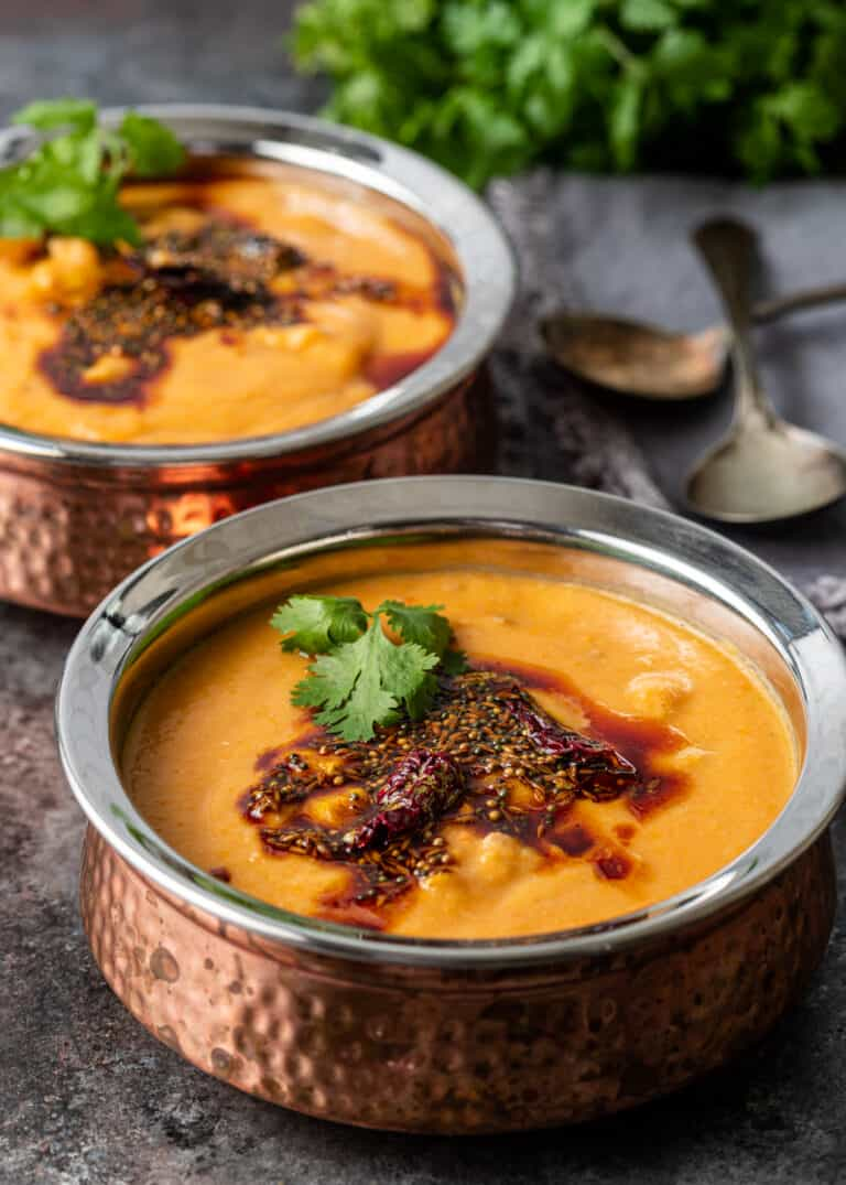 two copper soup bowls filled with turkey lentil curry