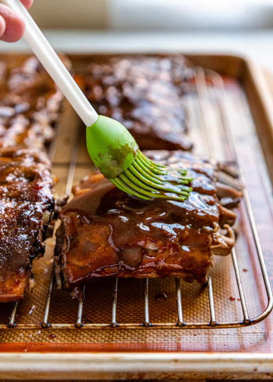 green silicone basting brush applying sauce to meat on baking sheet