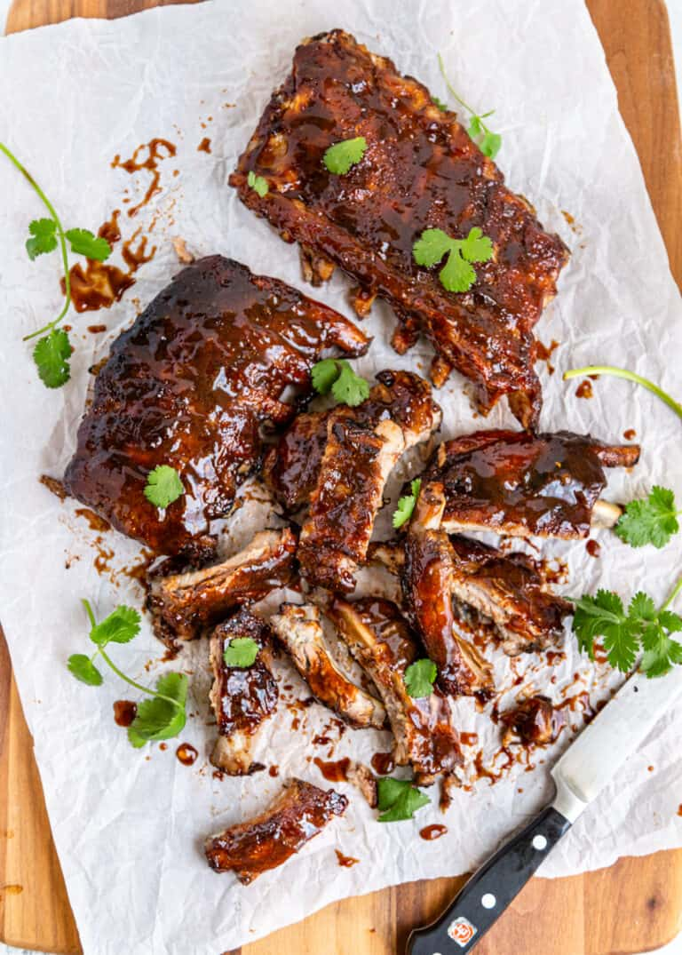 cutting apart sweet and sour ribs on white parchment paper